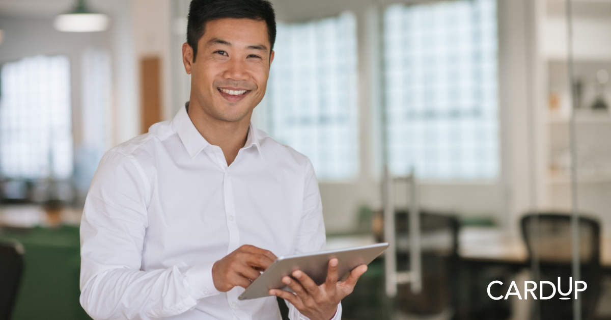 Businessman enjoys navigating CardUp platform via his ipad in office